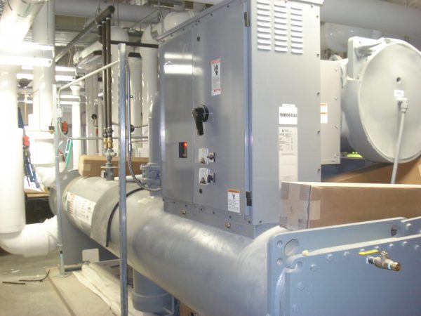 Large grey industrial chiller in basement utility room