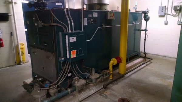 large black commercial boiler near yellow piping
