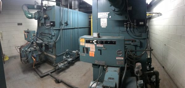 two industrial boilers side by side in a utility room